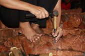 stock photo of woodcarving  - Hands of a master woodcarving buddhist sculpture for a temple - JPG