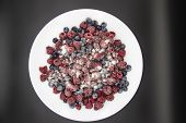 A Berry Mix In Sugar From Frozen Raspberries And Blueberries On The White Plate. A Frozen Berries Wi poster