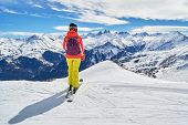 Female Skier With Colorful Clothes Looking At The Les Aiguilles Darves Peaks, From A Ski Slope High  poster