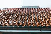 Tiled Clay Red Roof In The Snow. Medieval Old Roof In Winter In European Town. Clay Tiles In A Row.  poster