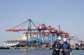 dock and port workers, container-ship and cranes across the water, commercial port