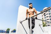 Young Man Doing Calisthenics On Pull-ups Bar Outdoors. poster