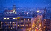 Prague Czech Republic. View at nighttime winter town with falling snow tower and broach cathedral. I poster