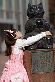 stock photo of lolita  - japanese lolita hugging cat statue in Tokyo - JPG
