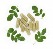 stock photo of oleifera  - Moringa oleifera capsule with green fresh leaves on white background - JPG