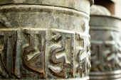 Spinning Buddhist Prayer Drums With Ancient Mantras Close Up. Fixture For Traditionhal Buddist Praye poster