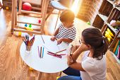 Beautiful teacher and toddler boy drawing draw using colored pencils at kindergarten poster