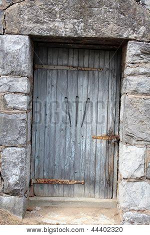Old door with rusty hardware in stone building