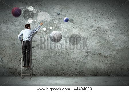 Image of businessman drawing planets on wall
