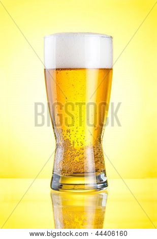 Glass Of Fresh Lager Beer Close-up With Froth Over Yellow Background