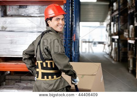 Portrait of smiling warehouse worker pushing handtruck with cardboard boxes