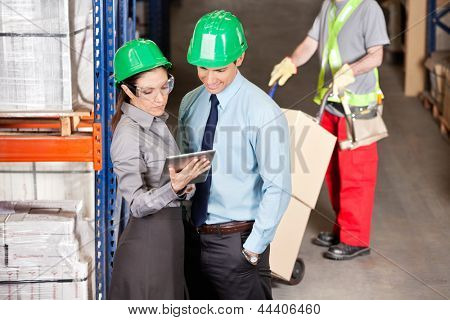 Supervisors using digital tablet with foreman working at warehouse