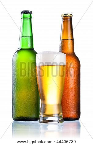Brown And Green Bottles Full Of Condensate And Covered With A Glass Of Fresh Cold Beer Isolated On A