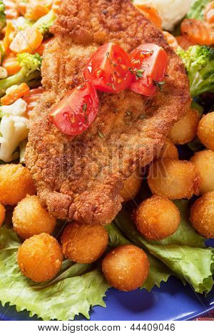 Viener schnitzel, breaded steak with potato crockets and vegetables