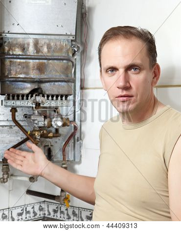 The man with a wrench thinks of repair of a gas water heater..