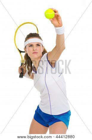 Confident Female Tennis Player Serving Ball