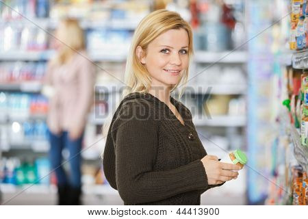 Portrait of smiling young Caucasian woman shopping at supermarket