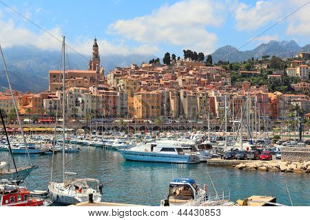 Colorful houses, church and marina with yachts and boats in Menton - town on French Riviera in France.