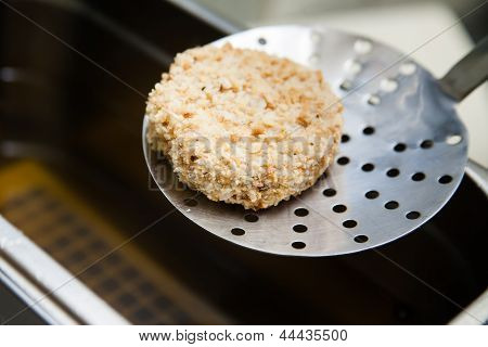 Raw Kiev chicken on  perforated spoon