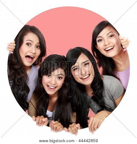 Grupo de mulheres bonitas sorrindo espiando através do furo do círculo