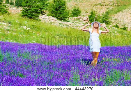 Attractive woman with closed eyes enjoying bright warm sun light, spending time on beautiful fresh lavender field, purple summer flowers, happiness concept