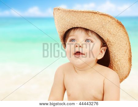 Closeup portrait of little naked cowboy wearing stetson hat over seascape background, happy child playing on the beach, joy and fun concept