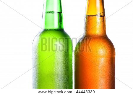 Topping Of Green And Brown Bottle With Light Beer With Condensate On Isolated White Background