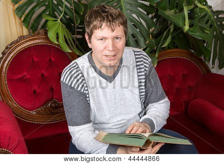 Young Man Reading Book On Red Couch Indoor