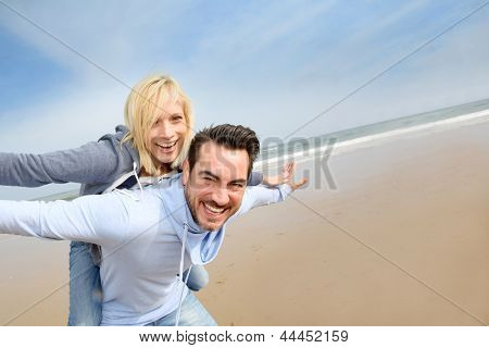 Middle-aged couple having fun on a sandy beach