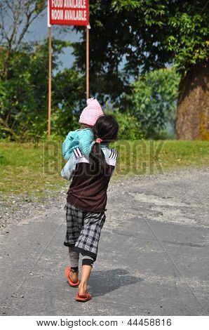 Girl Holds Baby Walk In The Stree