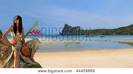 Woman in sarong on a coconut tree at the  beach  in Thailand