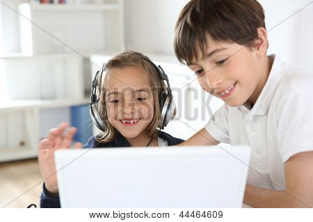 Portrait of kids waving at webcamera with laptop