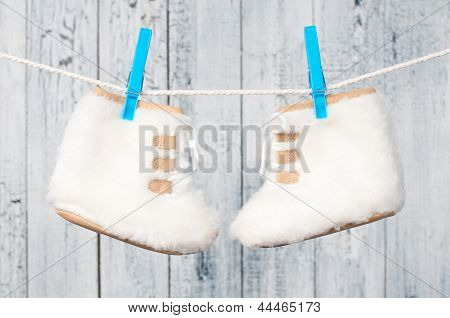 Children's Boots Hanging On A Clothesline.