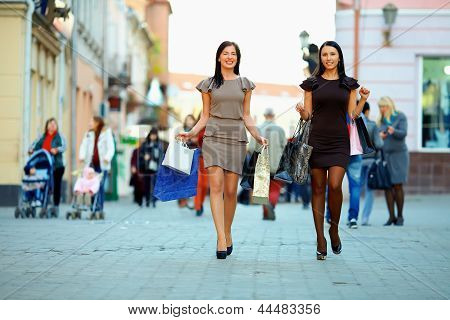 Two Elegant Women Walking The Crowded City With Shopping Bags