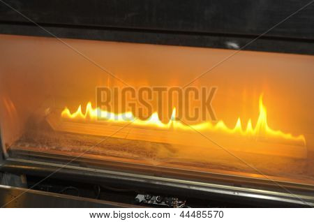 Burning gas fire at fireplace in the restaurant