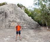 The tourist against pyramid ruins Mexico. Archeologic zone Kabah.