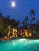 full moon night view of a swimming pool on a beautiful resort at Koh Samui island Thailand