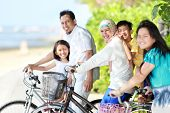 stock photo of muslim man  - Happy asian family riding bikes in the beautiful morning at the beach - JPG