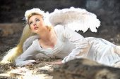 stock photo of cleavage  - Beautiful Angel Woman Lies In Old Theatre - JPG