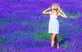 Cute blond teen girl standing on purple lavender meadow, woman wearing white dress and hat take sun