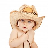 Cute baby boy wearing big cowboy hat isolated on white background, adorable child having fun indoors
