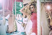 stock photo of funfair  - Fashion Model Posing On Carousel In Pretty Summer Dress - JPG