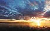 image of sunny season  - Dramatic Colorful sunset over ocean with sun - JPG