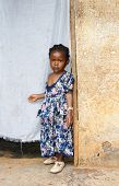 image of girl next door  - Cute but serious little black African girl in pink sunday dress next to her home door made of fabric - JPG