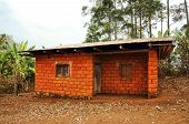 stock photo of mud-hut  - Typical red earth or soil brick with tin roof house for the workers and the like in Africa - JPG