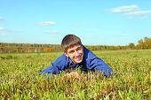 stock photo of wallow  - the happy teenager lying in the field - JPG
