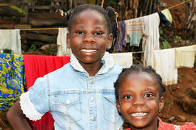 pic of overpopulation  - Real candid portraits of black African girls sisters with big smiles at home in front of clothesline in their backyard great for future of developing countries - JPG