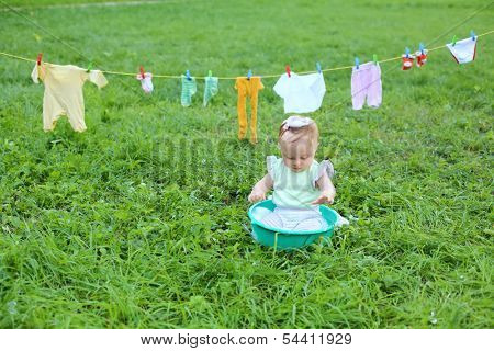The little girl in a small basin with foam near the rope with wash clothes