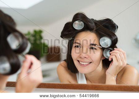 Woman In Hair Curlers Applying Eye Makeup