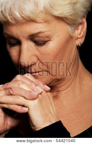 Portrait of old woman praying. Over black background.